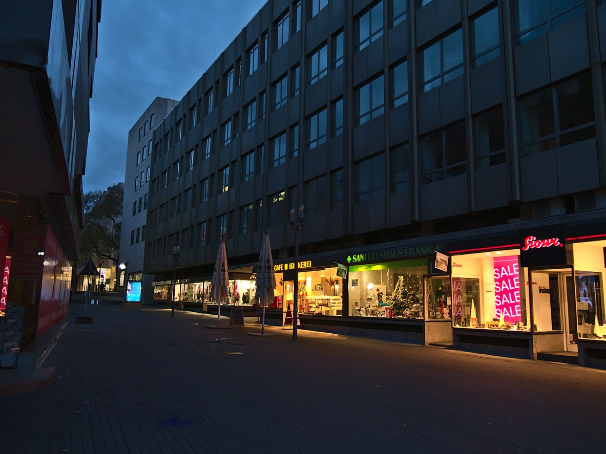 Deserted shopping street in city center with row of closed stores during Covid-19 lockdown and illuminated shop windows in evening in Christmas season